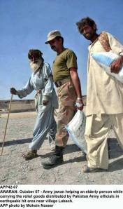 Army jawan helping an elderly person while carrying the relief goods distributed by Pakistan Army in earthquake